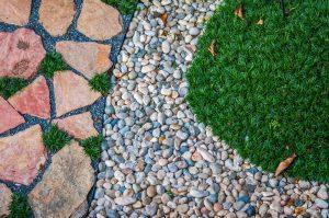 Mångfärgade stenar ligger dikt med gräsmatta och stenläggning.