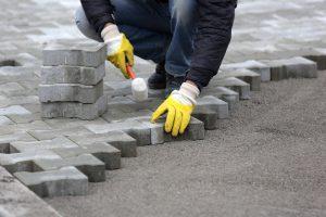 Stenläggning med gatusten och hammare.